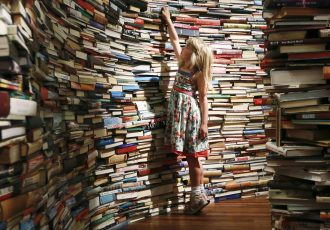 "Leona, 7, poses inside a labyrinth installation made up of 250,000 books titled ""aMAZEme"" by Marcos Saboya and Gualter Pupo at the Royal Festival Hall in central London July 31, 2012. REUTERS/Olivia Harris (BRITAIN - Tags: ENTERTAINMENT TPX IMAGES OF THE DAY) - RTR35PZS"