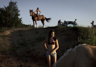 2011. RUSSIA. Vyalki, near Bykovo. Girls bathing their horses in a swimming pond next to an upscale dacha community.
